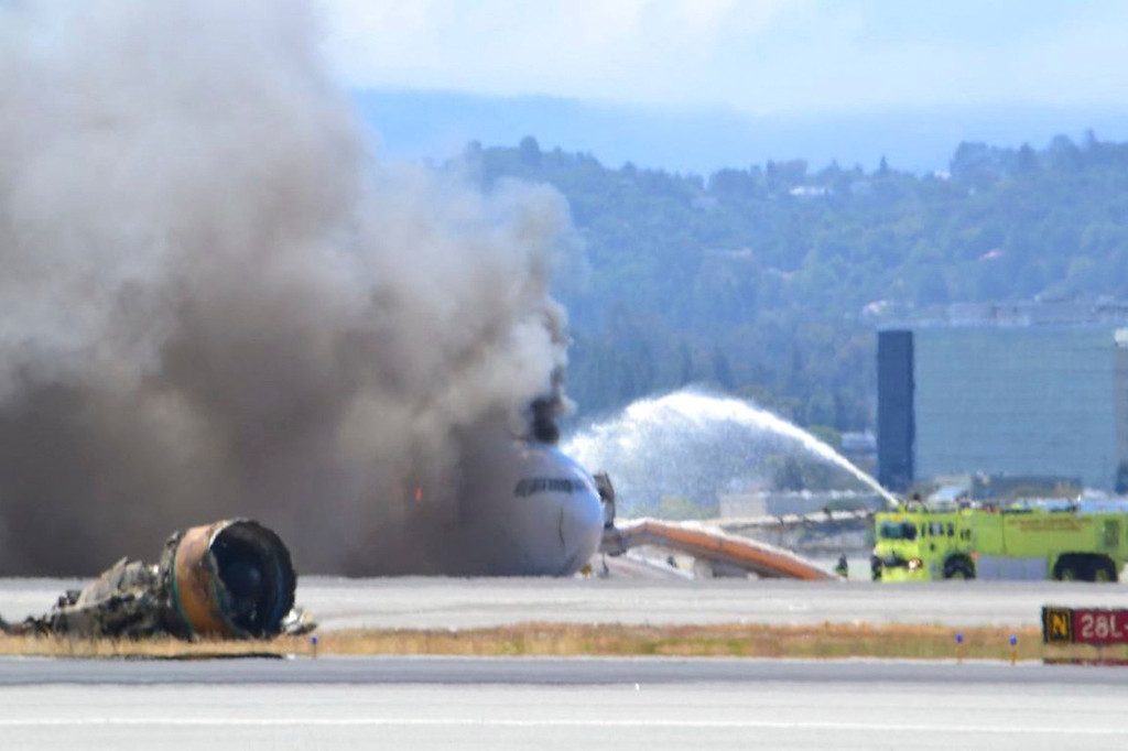 . Firefighters spray water on Asiana Airlines flight 214 as it sits on the runway burning at San Francisco Airport International Airport in this July 6, 2013 handout from the United States Coast Guard Southwest. The plane, with 307 people on board, crashed and burst into flames as it landed at San Francisco International Airport on Saturday after a flight from Seoul, and initial reports said two people were killed and more than 130 sent to hospitals.  REUTERS/Air Station San Francisco/United States Coast Guard Southwest/Handout via Reuters