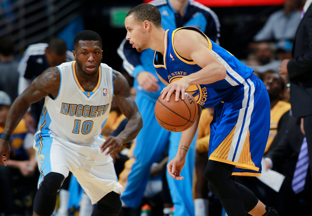 . Golden State Warriors guard Stephen Curry, right, works the ball inside as Denver Nuggets guard Nate Robinson covers in the fourth quarter of the Warriors\' 89-81 victory in an NBA basketball game in Denver on Monday, Dec. 23, 2013. (AP Photo/David Zalubowski)