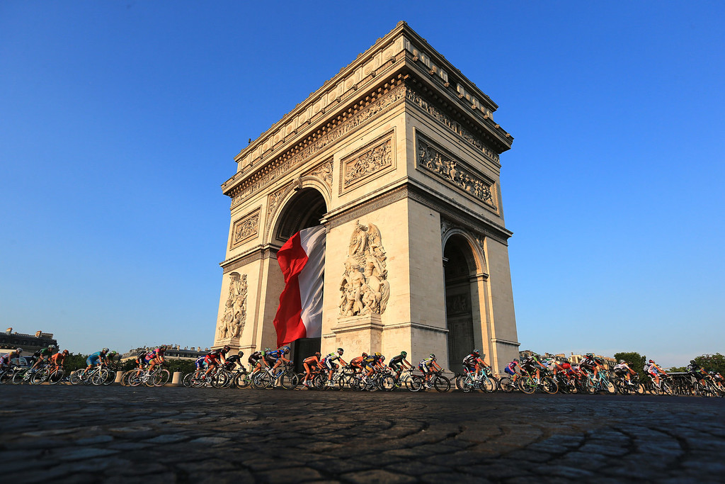 . The peloton rounds the Arc d\'Triomphe during the twenty first and final stage of the 2013 Tour de France, a processional 133.5KM road stage ending in an evening race around the Champs-Elysees, on July 21, 2013 in Paris, France.  (Photo by Doug Pensinger/Getty Images)