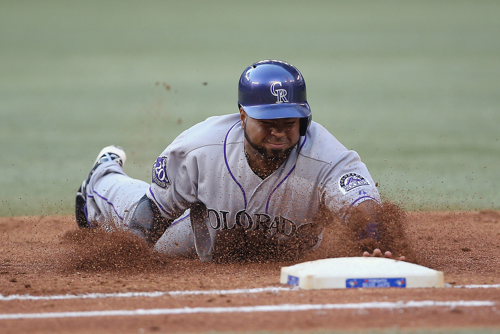. Wilin Rosario #20 of the Colorado Rockies dives back to first base to avoid being doubled off in the third inning during MLB game action against the Toronto Blue Jays on June 19, 2013 at Rogers Centre in Toronto, Ontario, Canada. (Photo by Tom Szczerbowski/Getty Images)