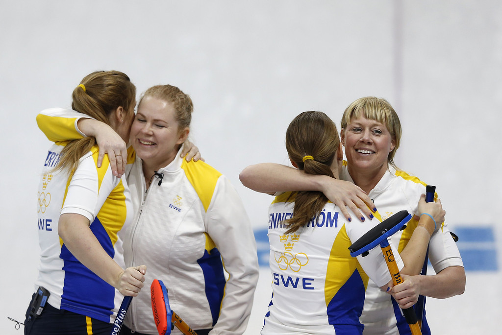 . Sweden\'s Maria Prytz (R) hugs teammate Maria Wennerstroem (2nd R) after winning their game during the women\'s curling round robin session 5 match between Switzerland and Sweden at the Ice Cube curling centre in Sochi on February 13, 2014 during the 2014 Sochi winter Olympics. ADRIAN DENNIS/AFP/Getty Images