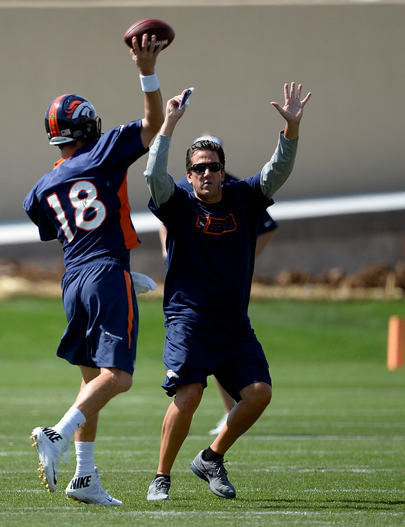 . Denver Broncos quarterbacks coach Greg Knapp tries to distract Denver Broncos quarterback Peyton Manning (18) in drills during practice August 25, 2014 at Dove Valley.(Photo by John Leyba/The Denver Post)