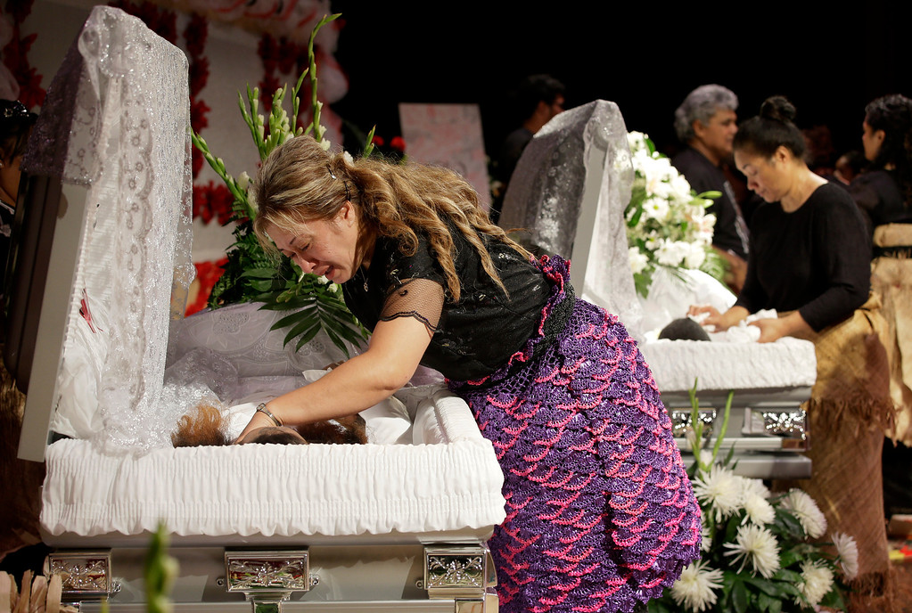 """. Poliana Taufa, front, the biological mother of Texas A&M redshirt freshman Polo Manukainiu, weeps as she leans over his casket during a memorial service for Manukainiu and his brother Andrew \""""Lolo\"""" Uhatafe, rear, Friday, Aug. 9, 2013, in Euless, Texas. The two were killed in a single car accident in New Mexico, on July 29. Also killed was 18-year-old Utah recruit Gaius \""""Keio\"""" Vaenuku. (AP Photo/Tony Gutierrez)"""