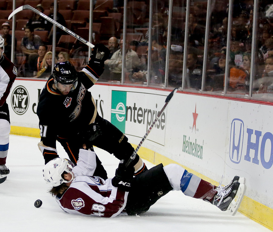 . Anaheim Ducks right wing Kyle Palmieri, top, trips Colorado Avalanche\'s Michell Heard during the second period of an NHL preseason hockey game in Anaheim, Calif., Sunday, Sept. 22, 2013. (AP Photo/Chris Carlson)