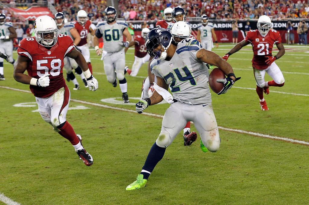 . Seattle Seahawks running back Marshawn Lynch (24) tries to avoid Arizona Cardinals inside linebacker Daryl Washington (58) during the second half of an NFL football game, Thursday, Oct. 17, 2013, in Glendale, Ariz. (AP Photo/Ross D. Franklin)