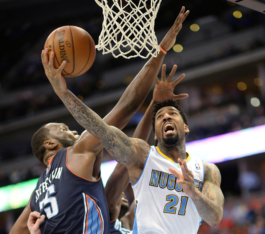 . Wilson Chandler of Denver Nuggets (21) missed the shot by the pressure of Al Jefferson of Charlotte Bobcats (25) in the second half of the game at Pepsi Center in Denver on Jan. 29, 2014. Charlotte won 101-98. (Photo by Hyoung Chang/The Denver Post)