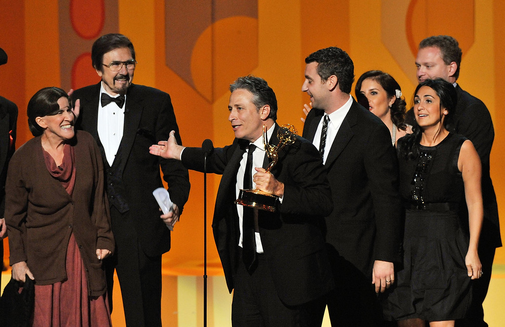 ". TV host Jon Stewart (C) accepts the Outstanding Variety, Music or Comedy Series award for ""The Daily Show With Jon Stewart\""onstage during the 60th Primetime Emmy Awards held at Nokia Theatre on September 21, 2008 in Los Angeles, California.  (Photo by Kevin Winter/Getty Images)"