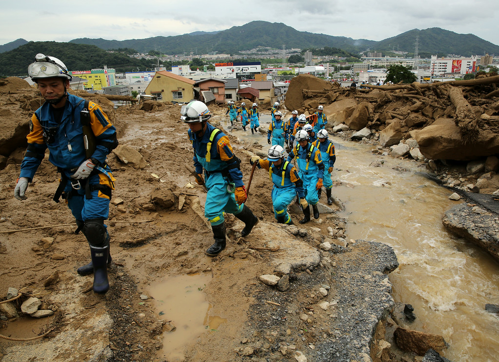 . Members of Police arrive to doing rescue work in an area damaged by a landslide caused by torrential rain at the site of a landslide in a residential area on August 20, 2014 in Hiroshima, Japan.  (Photo by Buddhika Weerasinghe/Getty Images)