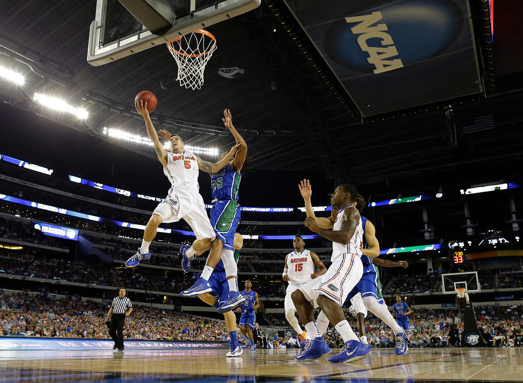 . Florida\'s Scottie Wilbekin (5) shoots as Florida Gulf Coast\'s Sherwood Brown (25) defends during the second half of a regional semifinal game in the NCAA college basketball tournament, Saturday, March 30, 2013, in Arlington, Texas. (AP Photo/Tony Gutierrez)