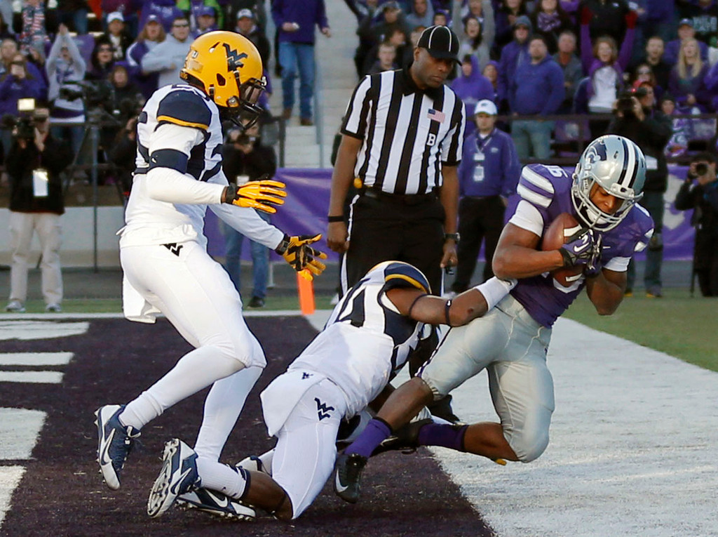 . Kansas State wide receiver Tyler Lockett, right, catches a touchdown pass while covered by West Virginia safety Darwin Cook, left, and cornerback Ishmael Banks during the second half of an NCAA college football game in Manhattan, Kan., Saturday, Oct. 26, 2013. Kansas State won 35-12. (AP Photo/Orlin Wagner)