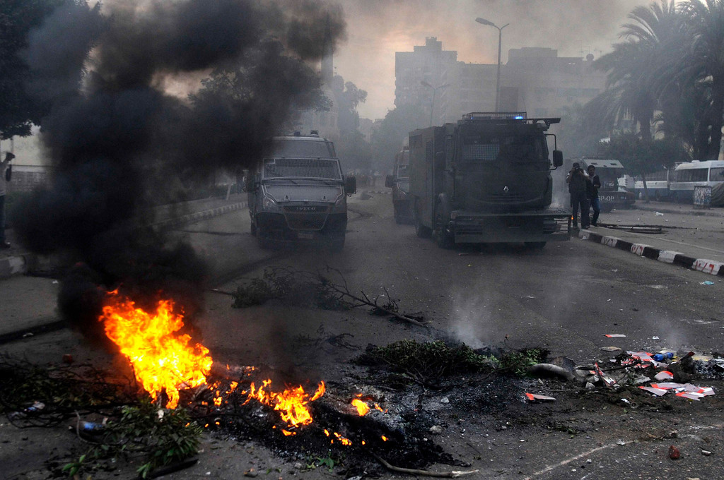 . Egyptian anti-riot police forces advance amid smoke and burning objects allegedly set on fire by supporters of the Muslim Brotherhood during clashes near the Koubbeh Palace, in Cairo, Egypt, 29 November 2013.   EPA/TAREK WAJEH/ALMASRY ALYOUM