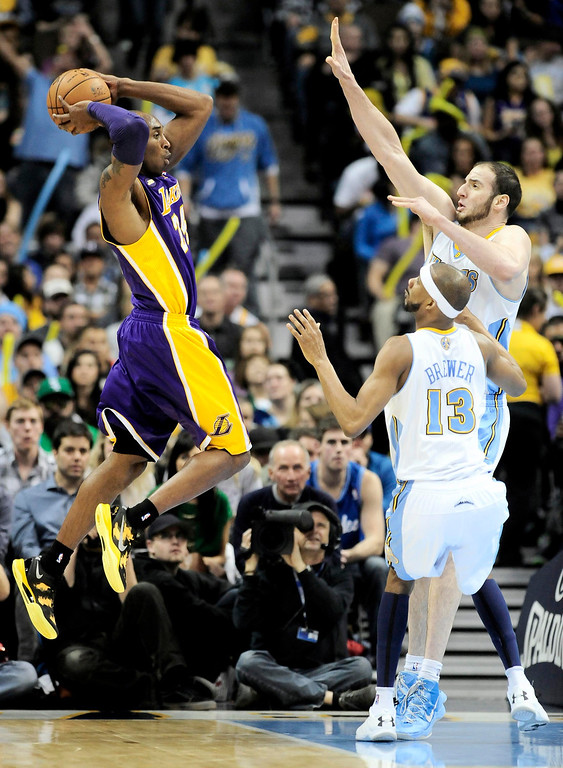 . Los Angeles Lakers\' Kobe Bryant (L) looks to pass the ball over Denver Nuggets\' Corey Brewer and Kosta Koufos (R) during their NBA basketball game in Denver, Colorado February 25, 2013.   REUTERS/Mark Leffingwell