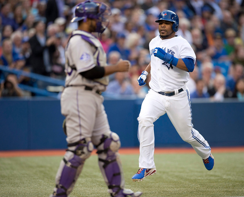 . Toronto Blue Jays\' Edwin Encarnacion scores on a Adam Lind single, as  Colorado Rockies catcher Wilin Rosario looks on during the first inning of an inter-league baseball game in Toronto on Tuesday June 18, 2013.   (AP Photo/The Canadian Press, Frank Gunn)