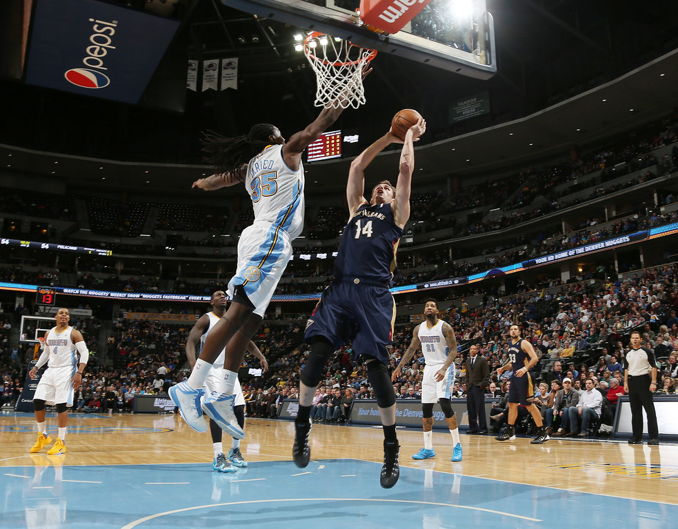 . New Orleans Pelicans center Jason Smith, right, goes up for a shot as Denver Nuggets forward Kenneth Faried covers in the third quarter of the Nuggets\' 102-93 victory in an NBA basketball game in Denver on Sunday, Dec. 15, 2013. (AP Photo/David Zalubowski)