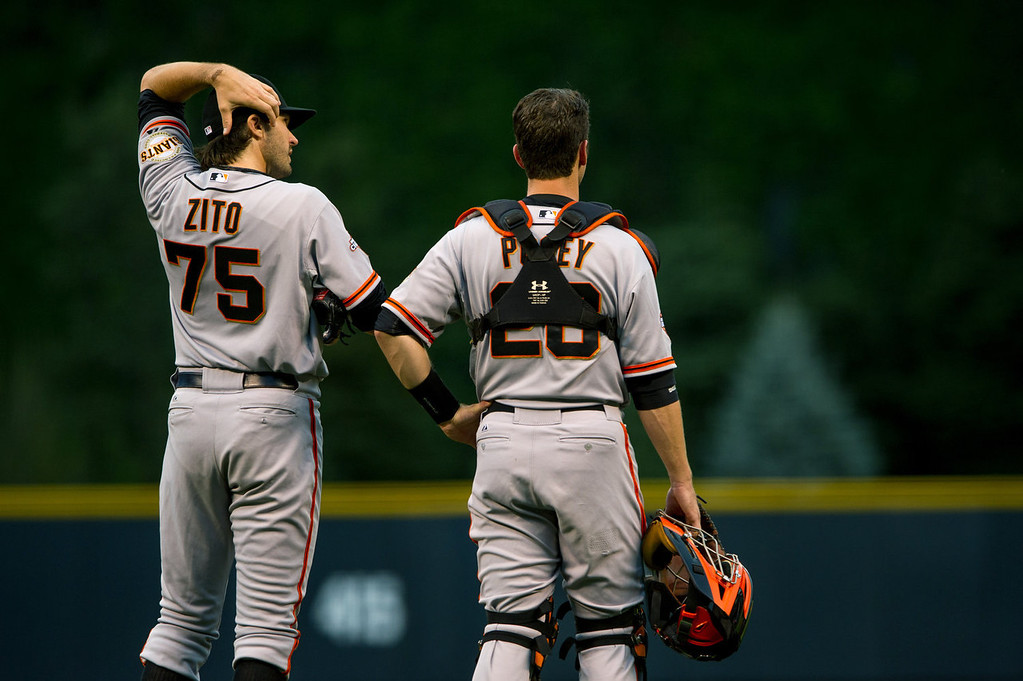 . Barry Zito #75 and Buster Posey #28 of the San Francisco Giants look on as Hunter Pence #8 (not pictured) is looked after by trainers after he slammed into the outfield wall during a game at Coors Field on August 26, 2013 in Denver, Colorado. (Photo by Dustin Bradford/Getty Images)
