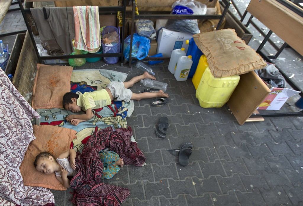 """. Displaced Palestinian children rest at the Abu Hussien UN school in the Jabalia refugee camp in the northern Gaza Strip after the area was hit earlier in the morning by Israeli shelling on July 30, 2014. Israeli bombardments early on July 30 killed \""""dozens\"""" of Palestinians in Gaza, including at least 16 at a UN school, medics said, on day 23 of the Israel-Hamas conflict. AFP PHOTO / MAHMUD HAMS/AFP/Getty Images"""