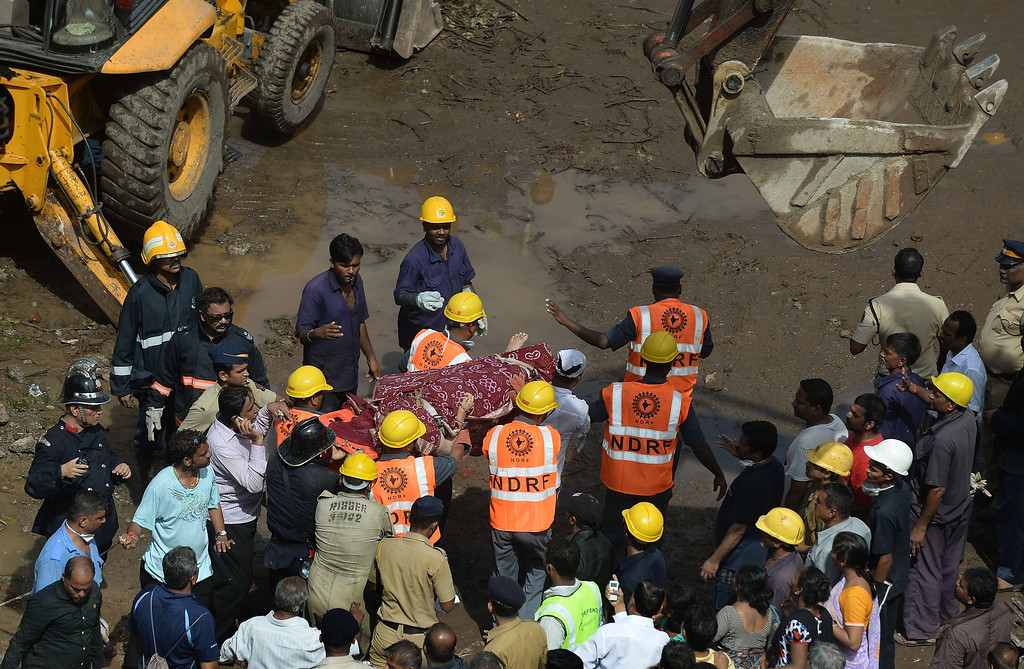 . Firefighters and rescue workers carry a body from the site of a building collapse in Mumbai on September 27, 2013.   AFP PHOTO/ PUNIT PARANJPE/AFP/Getty Images