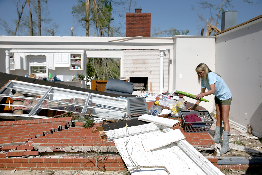 . Cherie Bell helps her parents  salvage items from their home that was damaged on Monday by a tornado on April 30, 2014 in Louisville, Mississippi. Deadly tornadoes ripped through the region starting on April 27 leaving more than two dozen dead. The storm system has also brought severe flooding to Florida\'s Panhandle.  (Photo by Joe Raedle/Getty Images)