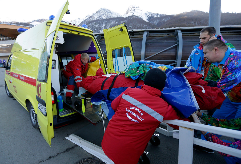 . A track worker is loaded into an ambulance after he was injured when a forerunner bobsled hit him just before the start of the men\'s two-man bobsled training at the 2014 Winter Olympics, Thursday, Feb. 13, 2014, in Krasnaya Polyana, Russia. (AP Photo/Charlie Riedel)