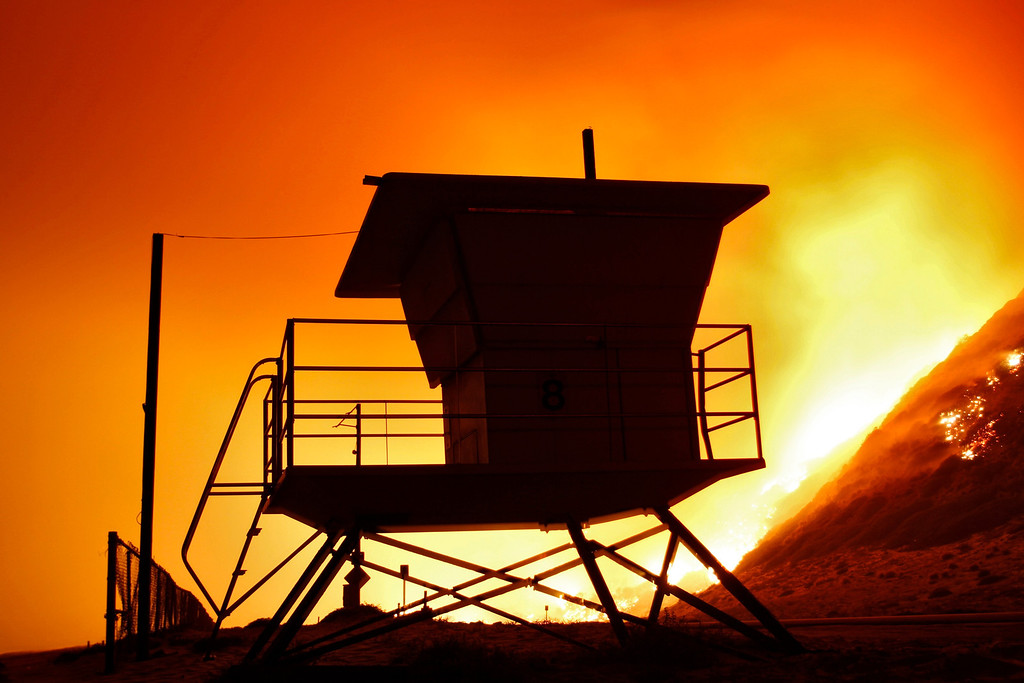 . A lifeguard tower stands on the beach at Point Mugu State Park as the Springs Fire burns on the nearby hillside May 3, 2013.  REUTERS/Jonathan Alcorn