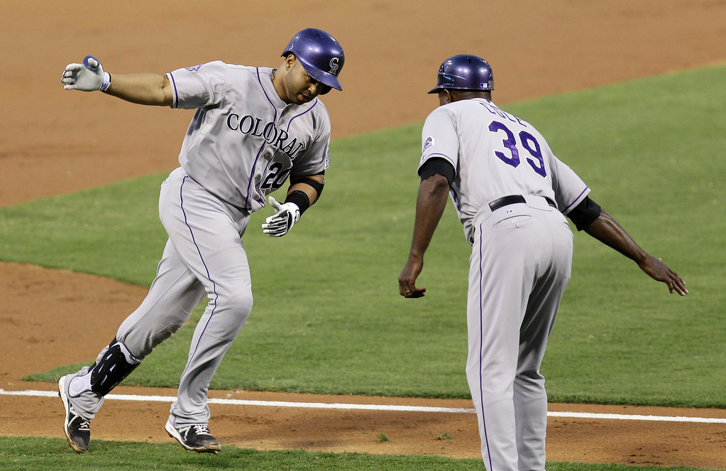 . Colorado Rockies\' Willin Rosario, left, is cheered on by Stu Cole while running the bases after hitting a home run in the third inning against the Philadelphia Phillies in a baseball game, Tuesday, Aug. 20, 2013, in Philadelphia. (AP Photo/Laurence Kesterson)
