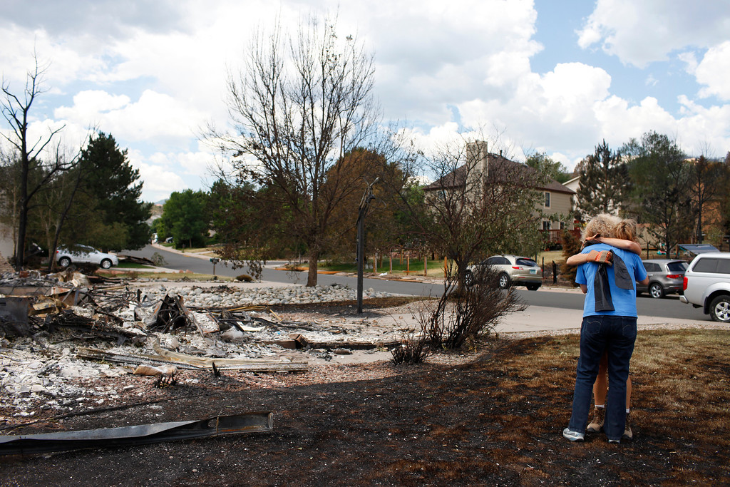 . Carla Albers, facing away from camera, hugs a neighbor after seeing the remnants of her family\'s home in the Mountain Shadows subdivision on Sunday, July 1, 2012. Stephen Mitchell, The Denver Post