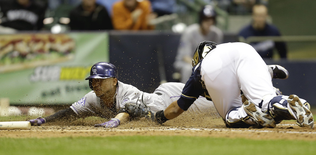 . MILWAUKEE, WI - APRIL 3:  Carlos Gonzalez #5 of the Colorado Rockies slides head first into home plate while getting tagged out by Martin Maldonado #12 of the Milwaukee Brewers during the top of the 8th inning at Miller Park on April 3, 2013 in Milwaukee, Wisconsin. (Photo by Mike McGinnis/Getty Images)