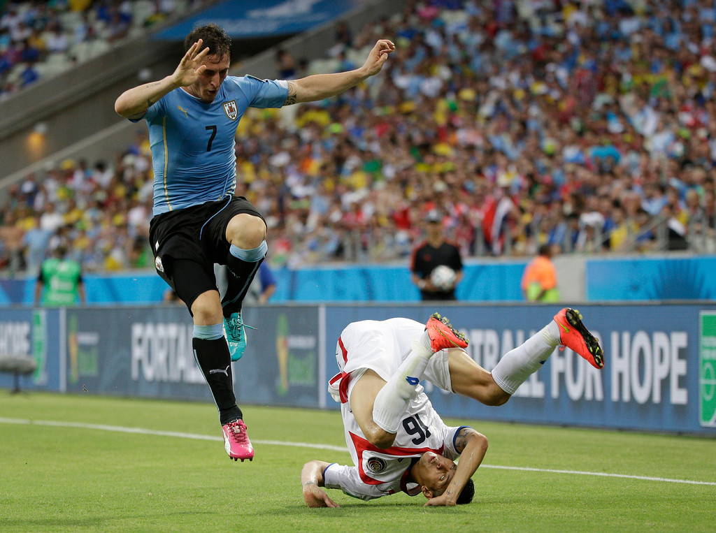 . Costa Rica\'s Cristian Gamboa, right, is sent tumbling by a challenge from Uruguay\'s Cristian Rodriguez during the group D World Cup soccer match between Uruguay and Costa Rica at the Arena Castelao in Fortaleza, Brazil, Saturday, June 14, 2014.  (AP Photo/Christophe Ena)