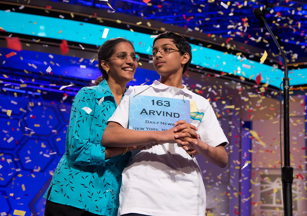 """. Arvind Mahankali, 13, of Bayside Hills, N.Y., is congratulated by his mother Bhavani, as confetti falls after he won the National Spelling Bee by spelling the word \""""knaidel\"""" correctly on Thursday, May 30, 2013, in Oxon Hill, Md. (AP Photo/Evan Vucci)"""