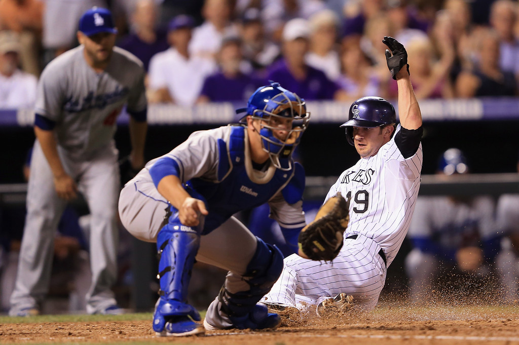 . Charlie Blackmon #19 of the Colorado Rockies slides home to score as catcher Tim Federowicz #18 of the Los Angeles Dodgers awaits the throw after Jhoulys Chacin #45 of the Colorado Rockies hit an RBI single to rightfield in the fifth inning at Coors Field on September 3, 2013 in Denver, Colorado.  (Photo by Doug Pensinger/Getty Images)