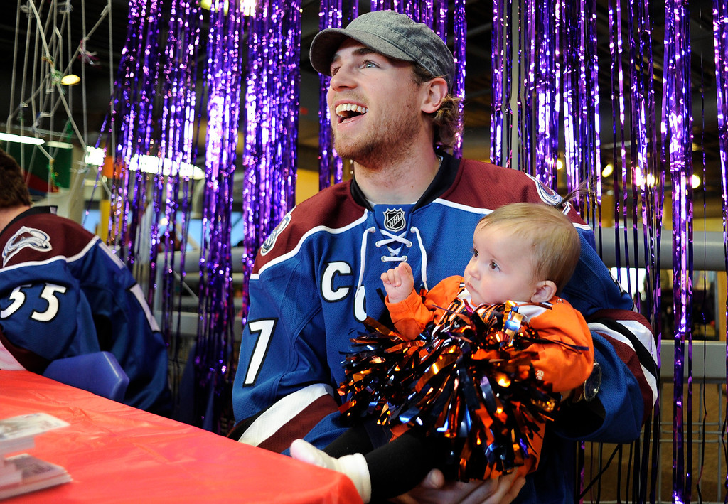 . Colorado Avalanche player Ryan O\'Reilly smiles as he gets his photo taken with Sydney Boettiger 6-months old after signing autographs for kids at the Children\'s Museum during their Trick o Treat Street. The day is filled with exciting events for the kids with crafts, a carnival theme and goodies for the kids to collect. John Leyba, The Denver Post