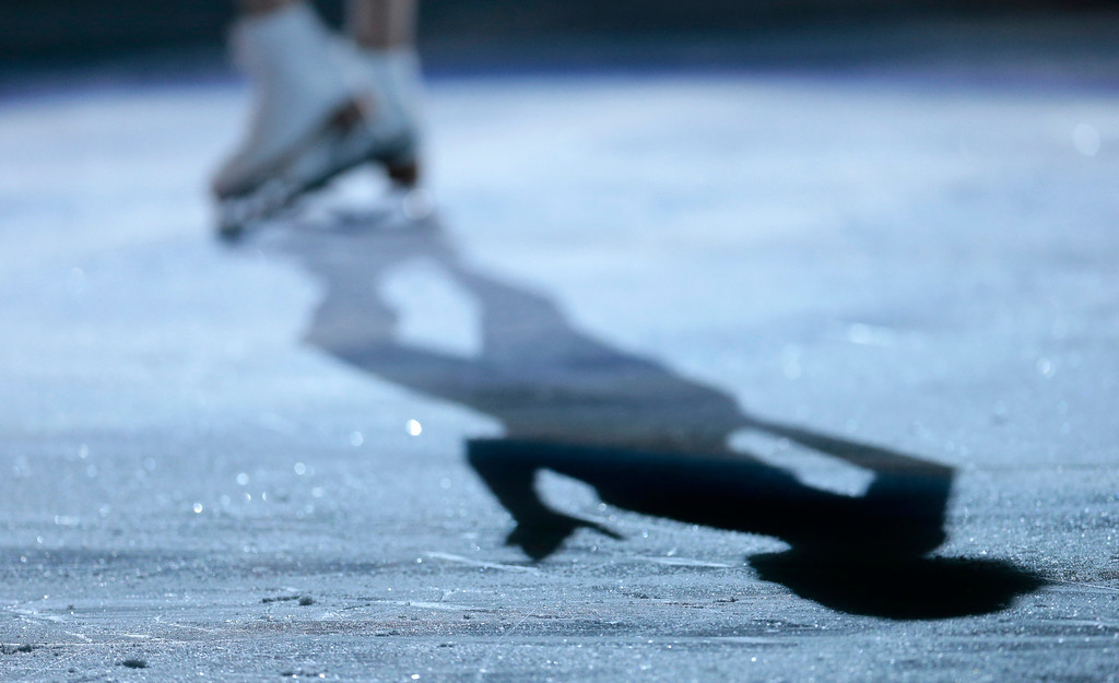 . Carolina Kostner of Italy casts a shadow as she begins her routine in the figure skating exhibition gala at the Iceberg Skating Palace during the 2014 Winter Olympics, Saturday, Feb. 22, 2014, in Sochi, Russia. (AP Photo/Ivan Sekretarev)