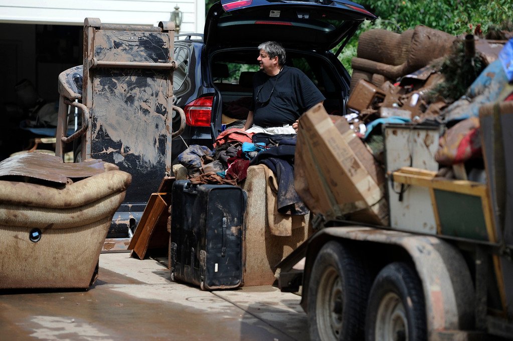 . BOULDER, CO - SEPTEMBER 13: Chris Vacek, stands on his driveway in Boulder Colorado Friday morning, September 13, 2013 next to his family\'s personal belongings, drenched and covered in mud. Vacek\'s basement was flooded out from the past days torrential rainfall, everything in the basement was destroyed. (Photo By Andy Cross/The Denver Post)