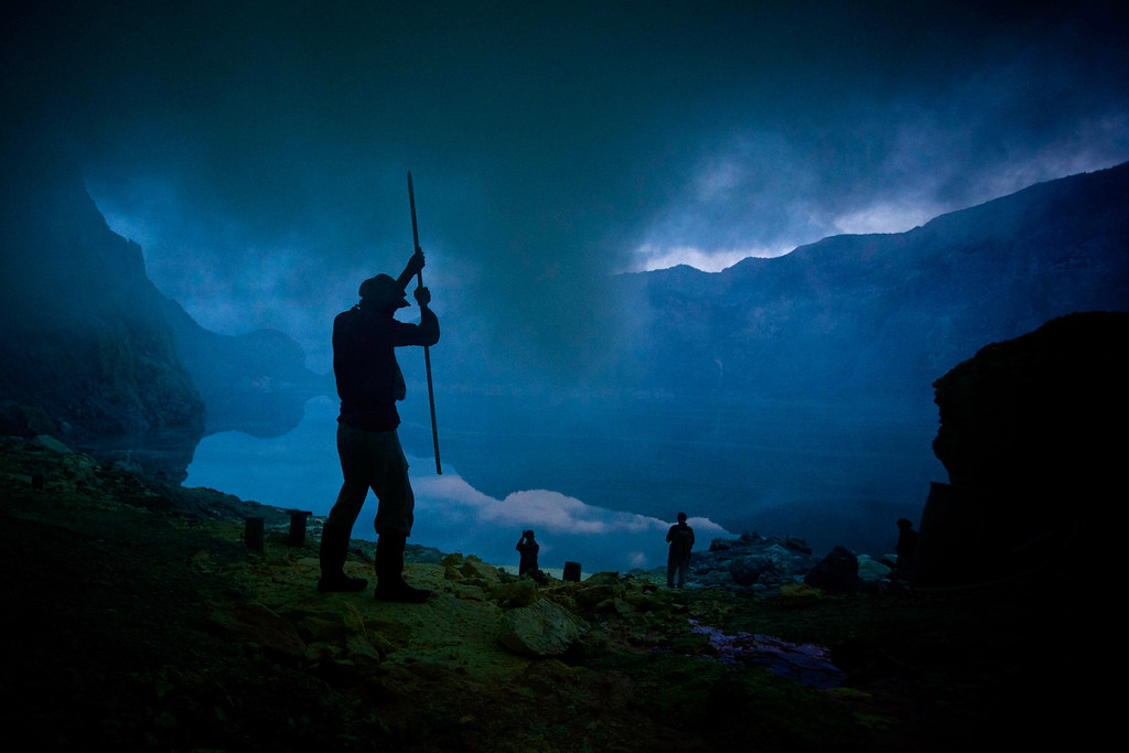 . A miner uses a pole to extract sulphur from a pipe at the flow crater during an annual offering ceremony on the Ijen volcano on December 17, 2013 in Yogyakarta, Indonesia. The ritual is performed by the sulfur miners of Mount Ijen who slaughter a goat and then bury the head in the crater of mount Ijenn. The sacrifice is performed to ward off potential disasters for the next year. The Ijen crater rises to 2,386m, with a depth of over 175m, making it one of the world\'s largest craters. Sulphur mining is a major industry in the region, made possible by an active vent at the edge of a lake, but the work is not without risks as the acidity of the water in the crater is high enough to dissolve clothing and cause breathing problems. (Photo by Ulet Ifansasti/Getty Images)