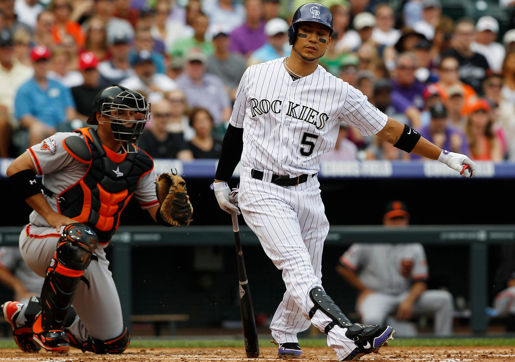 . Colorado Rockies\' Carlos Gonzalez, right, reacts after striking out as San Francisco Giants catcher Guillermo Quiroz looks on in the first inning of a baseball game in Denver on Sunday, June 30, 2013.  (AP Photo/David Zalubowski)
