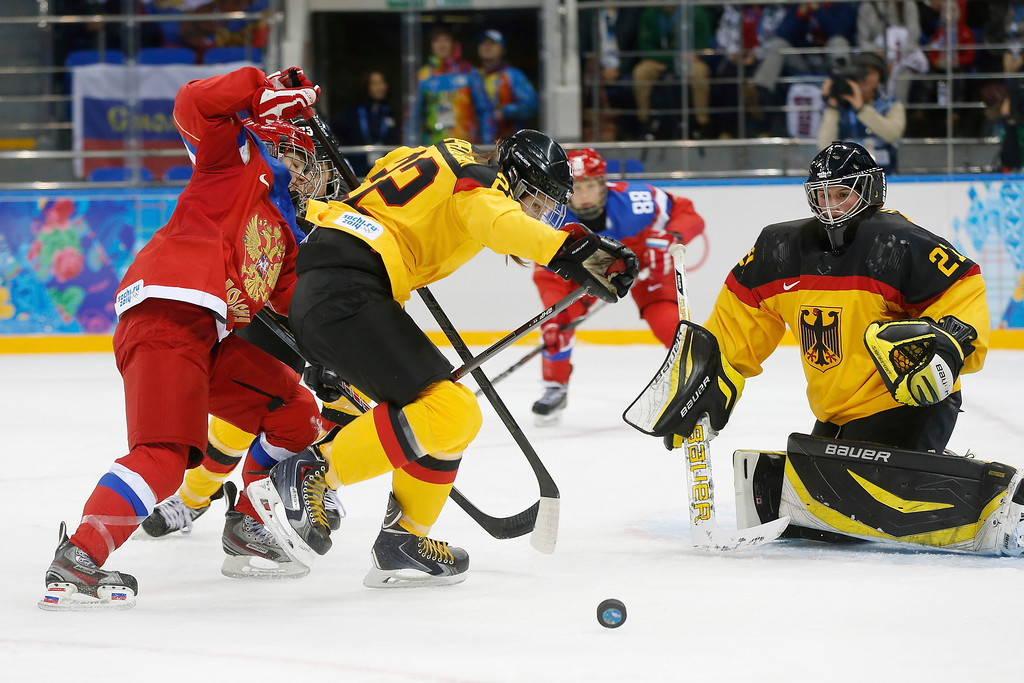 . Alexandra Vafina of Russia and Kerstin Spielberger of Germany battle for control as Goalkeeper Viona Harrer of Germany keeps an eye on the puck during the 2014 Winter Olympics women\'s ice hockey game at Shayba Arena, Sunday, Feb. 9, 2014, in Sochi, Russia. (AP Photo/Petr David Josek)