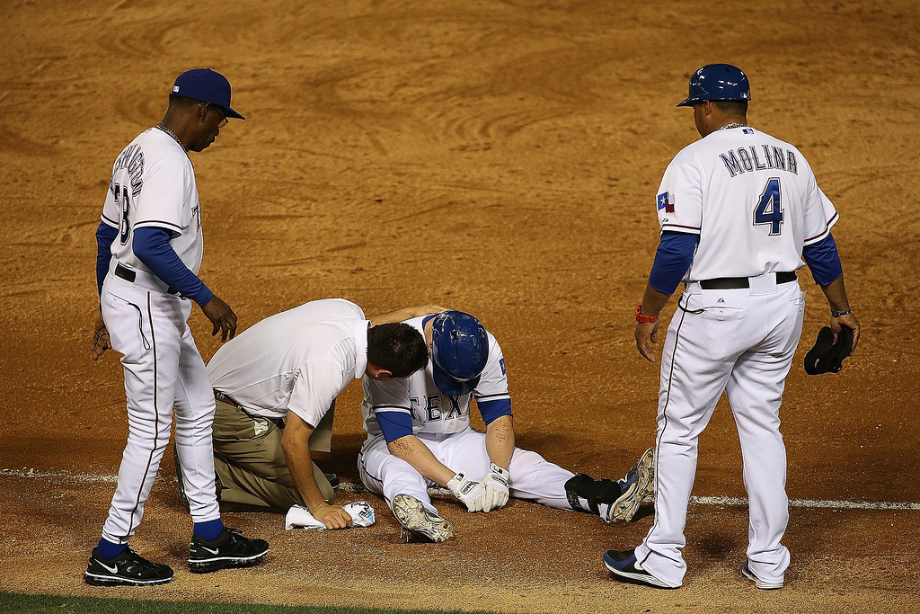 . Donnie Murphy #16 of the Texas Rangers is assisted by Rangers medical staff, manager Ron Washington #38 and Bengie Molina #4 after tripping on a run to first base against the Colorado Rockies at Globe Life Park in Arlington on May 7, 2014 in Arlington, Texas.  (Photo by Rick Yeatts/Getty Images)