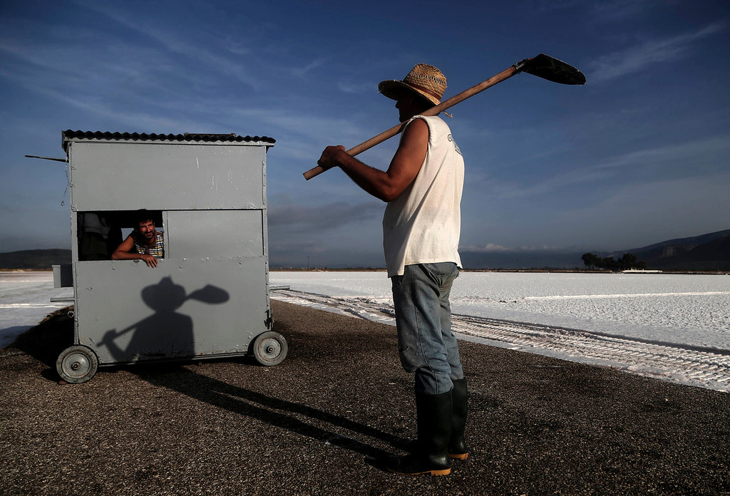 . Two workers talk at a production site in Messolongi, western Greece, on Monday Sept. 30, 2013. Salt lakes at Messolongi are used for production by solar evaporation. The facilities at the site are the largest saltworks in Greece, and are located at a protected wetland complex of estuaries and lagoons. (AP Photo/Dimitri Messinis)
