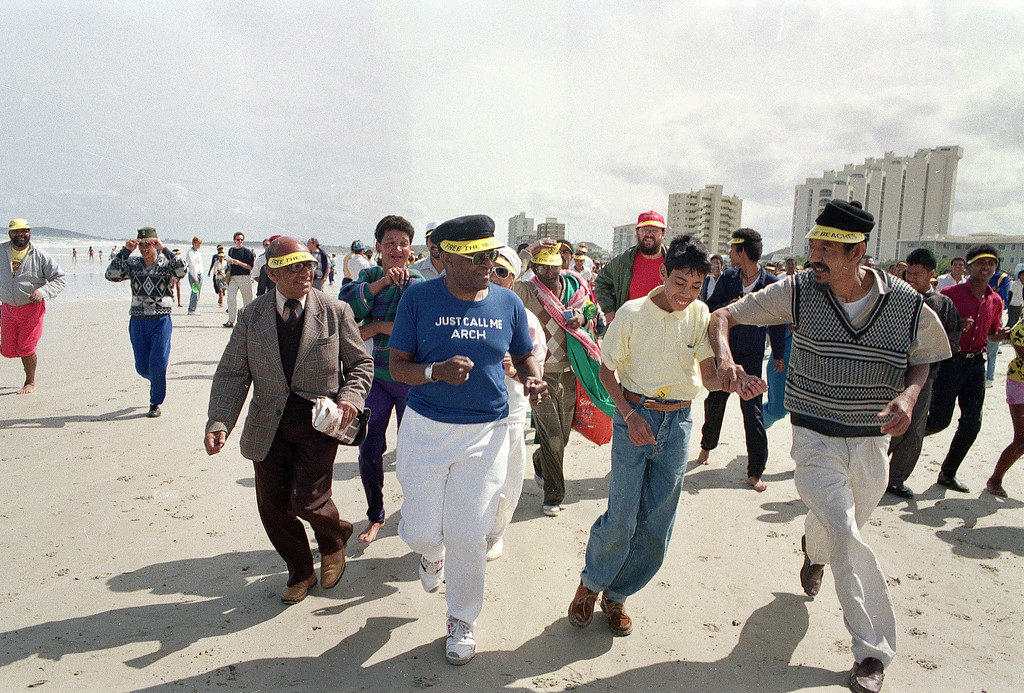 . Anglican Archbishop of Cape Town, Desmond Tutu (center) jogs along a whites only beach at the Strand, Saturday Sept. 30, 1989 with a crowd of supporters near Cape Town, as church organizations continued their campaign of defiance against Apartheid laws.  (AP Photo/Adil Bradlow)