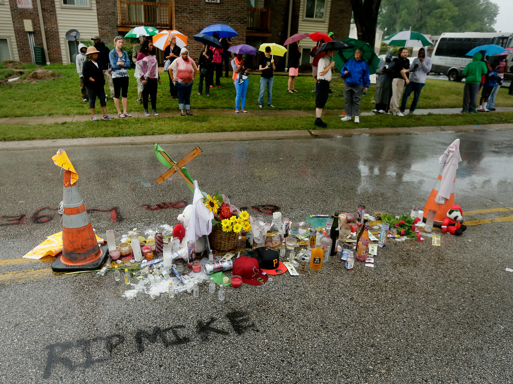 . People gather next to a makeshift memorial for Michael Brown Saturday, Aug. 16, 2014, located at the site where Brown was shot by police a week ago in Ferguson, Mo. Brown\'s shooting in the middle of a street following a suspected robbery of a box of cigars from a nearby market has sparked a week of protests, riots and looting in the St. Louis suburb. (AP Photo/Charlie Riedel)