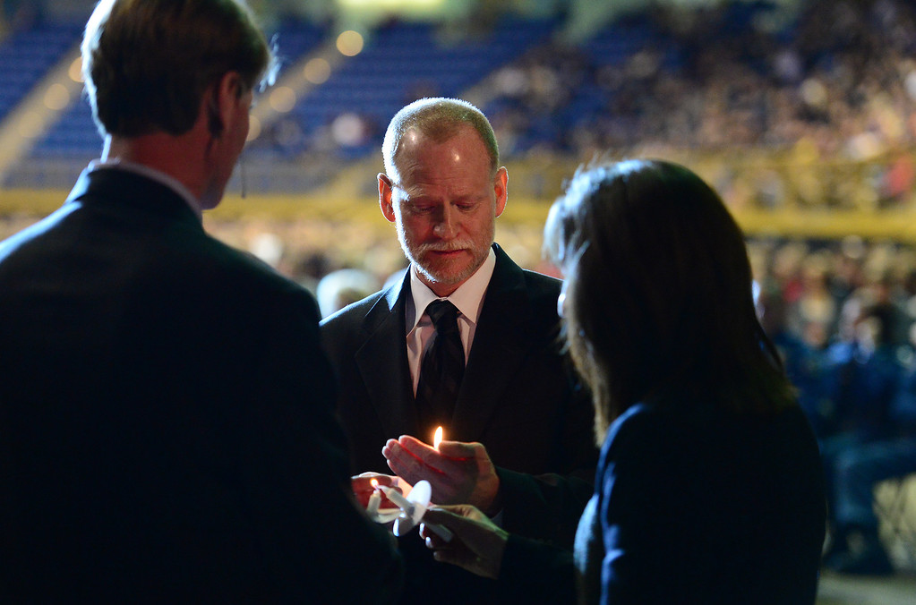 . Michael Davis, middle, lights a candle with his wife Desiree, right, and Reverend Steve Poos-Benson, left, as they prepare to hold up candles with thousands of others at the celebration of  life memorial service held for their daughter at the National Western Stock Show Event Center in Denver, Co on January 1, 2014.   Behind them at left is Governor John Hickenlooper.  Thousands of friends, family, students, and members of Claire\'s equestrian community turned out to pay tribute to Claire who was shot during the Arapahoe High School shooting in December. (Photo By Helen H. Richardson/ The Denver Post)