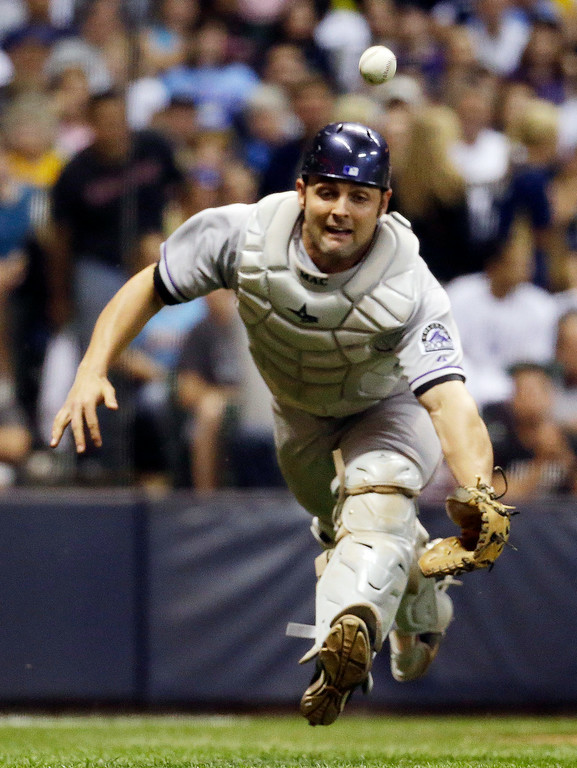 . Colorado Rockies catcher Michael McKenry can\'t catch a bunt foul by Milwaukee Brewers\' Martin Maldonado during the seventh inning of a baseball game Friday, June 27, 2014, in Milwaukee. (AP Photo/Morry Gash)