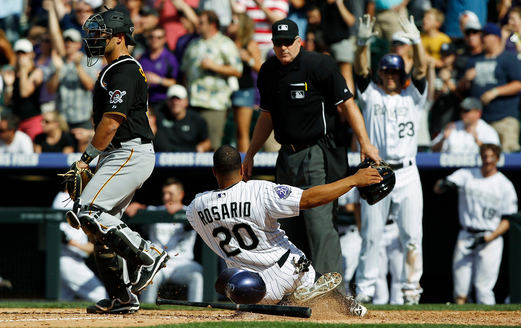 . Colorado Rockies\' Wilin Rosario (20) slides safely across home plate to score the go-ahead run on a double by Nolan Arenado as Pittsburgh Pirates catcher Tony Sanchez, left, looks on with home plate umpire Bill Welke in the seventh inning of the Rockies\' 3-2 victory in a baseball game in Denver, Sunday, Aug. 11, 2013. (AP Photo/David Zalubowski)