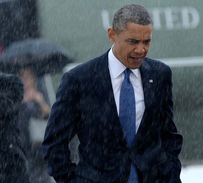 ". President Barack Obama walks in the rain prior to boarding Air Force One at Andrews Air Force Base in Md., Thursday, April 18, 2013. Obama is traveling to Boston to attend the ""Healing Our City: An Interfaith Service\"" dedicated to those who were gravely wounded or killed in Mondayís bombing near the finish line of the Boston Marathon. (AP Photo/Susan Walsh)"