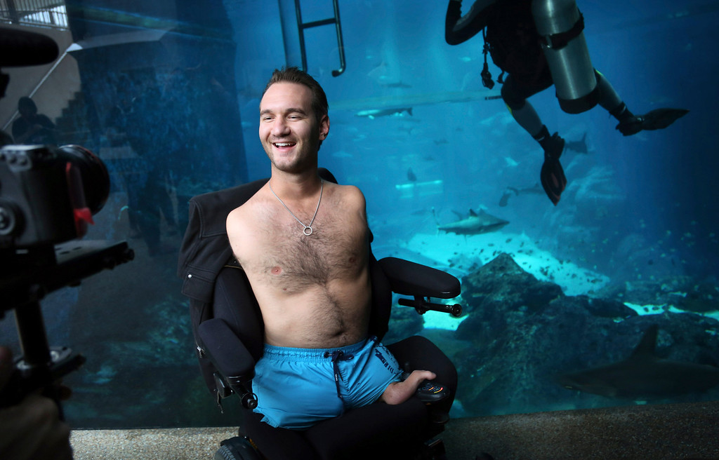 """. Nick Vujicic poses for his camera crew before diving with sharks Thursday, Sept. 5, 2013 in Singapore. Vujicic, a Serbian Australian evangelist and motivational speaker born with tetra-amelia syndrome, a rare disorder characterized by the absence of all four limbs, is in the city-state to give a motivational talk and was visiting  \""""The Shark Encounter at Marine Life Park\"""" at one of Singapore\'s main tourist attractions in Resorts World Sentosa. (AP Photo/Wong Maye-E)"""