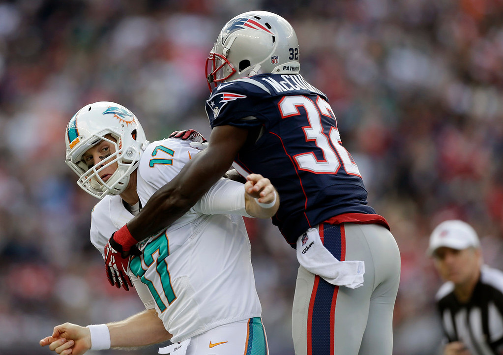 . New England Patriots free safety Devin McCourty (32) grabs Miami Dolphins quarterback Ryan Tannehill (17) during the first quarter of an NFL football game Sunday, Oct. 27, 2013, in Foxborough, Mass. (AP Photo/Steven Senne)