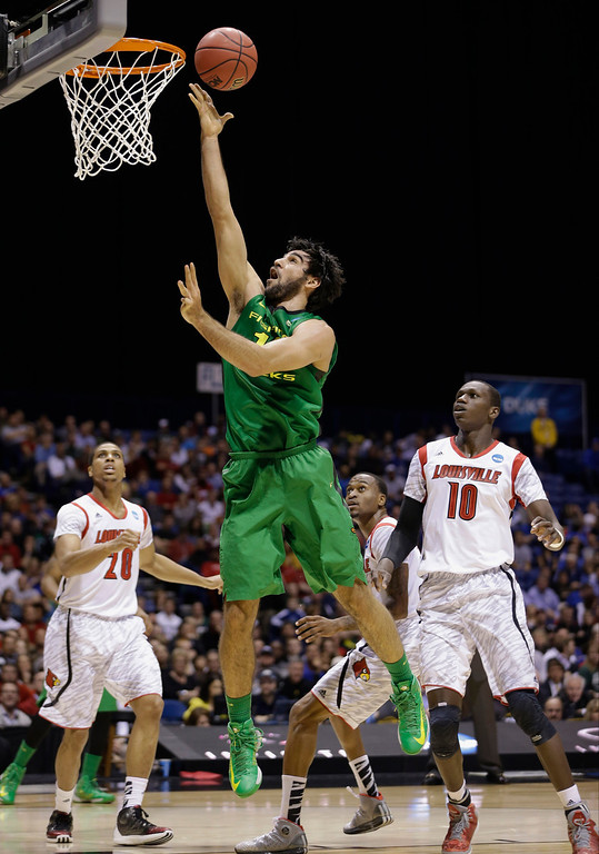 . Oregon forward Arsalan Kazemi goes up with a shot past Louisville\'s Gorgui Dieng (10) and Wayne Blackshear (20) during the first half of a regional semifinal against Louisville in the NCAA college basketball tournament, Friday, March 29, 2013, in Indianapolis. (AP Photo/Darron Cummings)