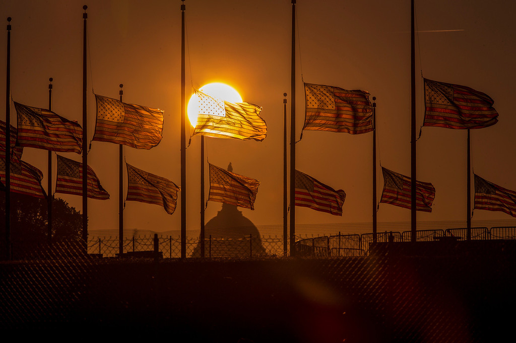 . The flags surrounding the Washington Monument fly at half-staff as ordered by President Barack Obama following the deadly shooting Monday at the Washington Navy Yard, Tuesday morning, Sept. 17, 2013, in Washington.  (AP Photo/J. Scott Applewhite, File)