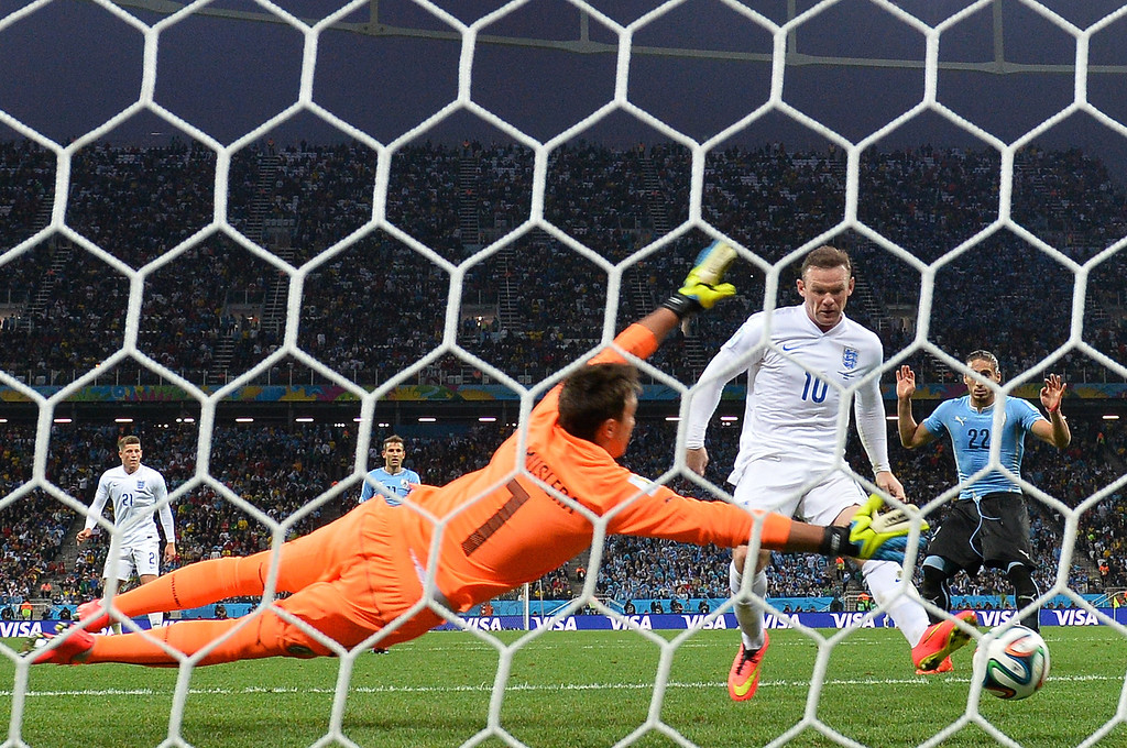 . England\'s forward Wayne Rooney (L) scores against Uruguay\'s goalkeeper Fernando Muslera (L) during a Group D football match between Uruguay and England at the Corinthians Arena in Sao Paulo during the 2014 FIFA World Cup on June 19, 2014.  BEN STANSALL/AFP/Getty Images