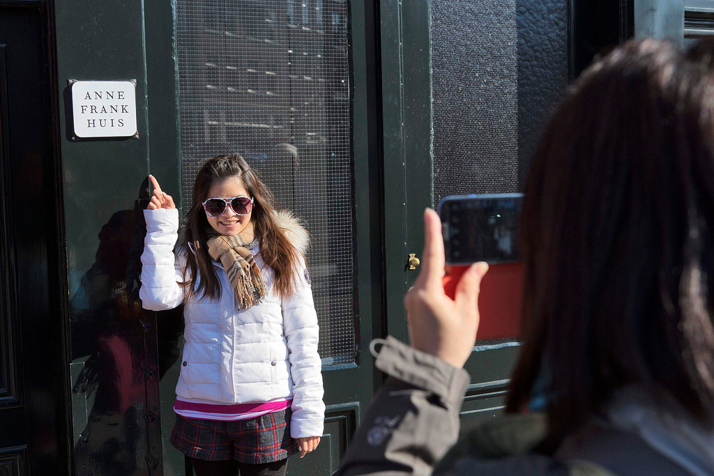 . A tourist takes a picture of her friend in front of the Anne Frank house in Amsterdam April 2, 2013. The Royal celebrations in the Netherlands this week put the country and the capital Amsterdam on front pages and television screens around the world with an orange splash. There\'s plenty to see and do in 48 hours in this compact city, where the world-famous Rijksmuseum only recently reopened after an extensive renovation. Picture taken April 2, 2013. REUTERS/Michael Kooren
